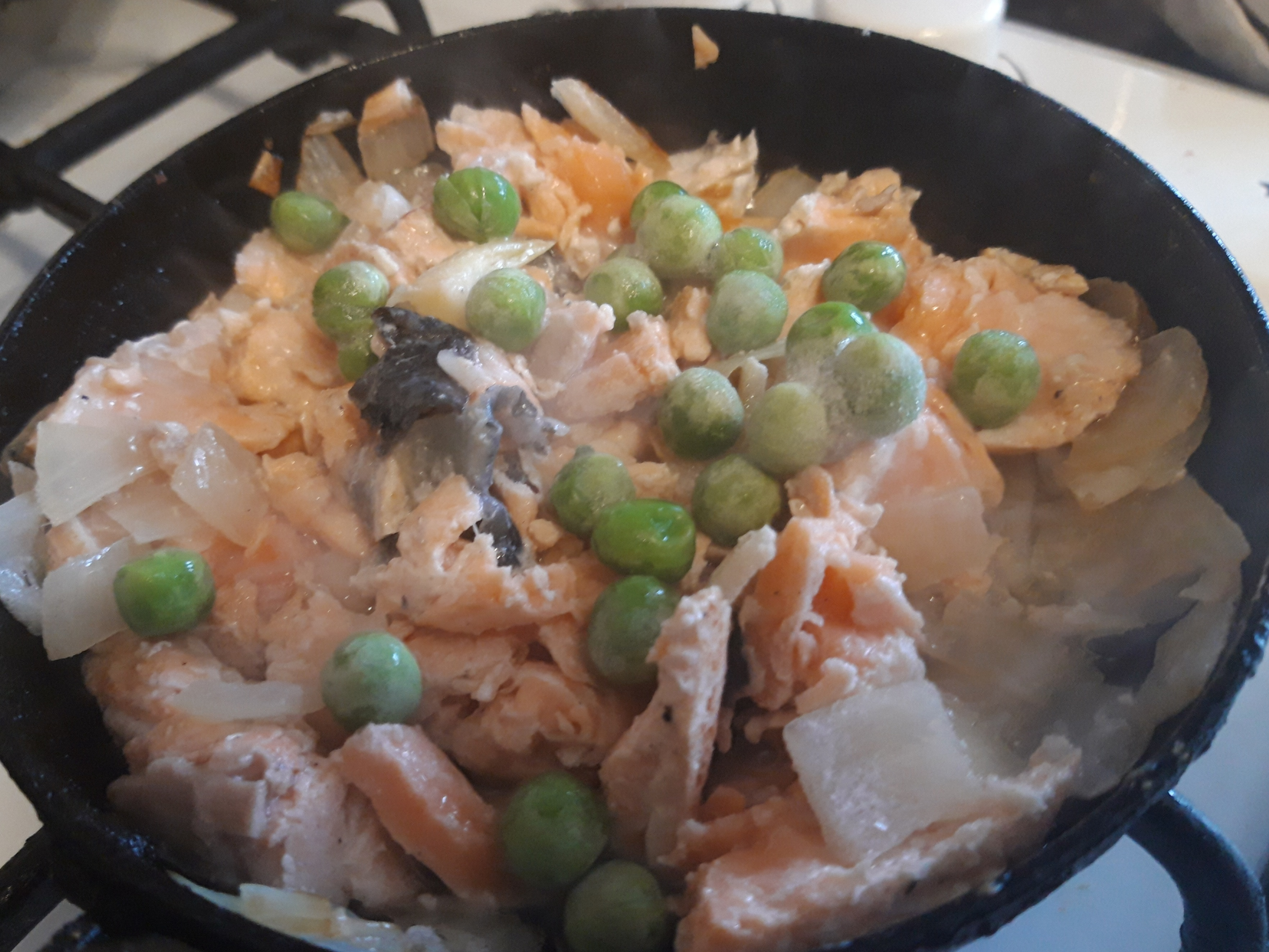 frying fresh salmon with onion and peas